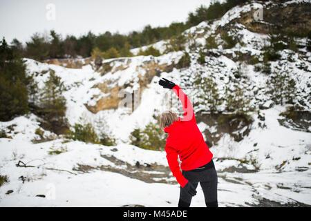 Mujer Senior correr en invierno la naturaleza.