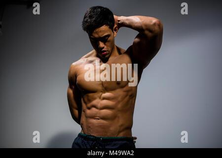 Un modelo asiático muscular fitness flexiona su musculoso abdomen ...