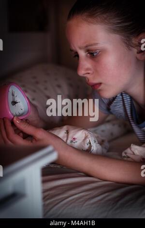 Ansioso chica incapaz de dormir por la noche mirando el reloj