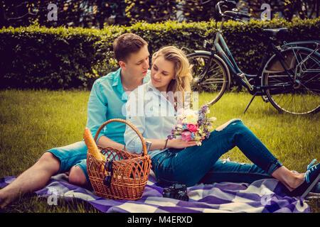 Encantadora pareja en picnik en un parque en un día soleado de verano. Foto de stock