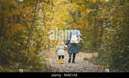Alegre hija con su mamá y el oso de peluche paseos en el parque de otoño, vista trasera