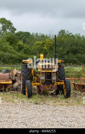 Viejo Tractor amarillo sobre residuos de tierra