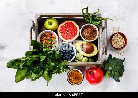 Comer alimentos saludables, Limpiar selección en caja de madera: frutas, verduras, semillas, súper alimento, cereales, vegetales de hojas sobre fondo blanco.