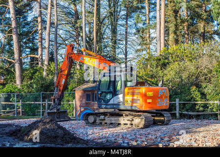 Gran naranja mecánica digger de pie sobre una plataforma de ladrillo núcleo duro de escombros en un sitio despejado de demolición se preparan para reurbanización residencial