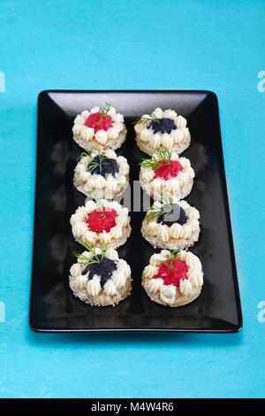 Placa con canapés de caviar rojo y negro adornado con eneldo.