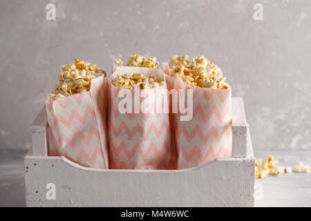 Golden caramelo pop corn en bolsas de papel en una caja de madera blanca.
