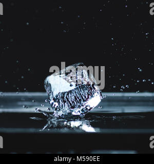 Cubo de hielo derritiéndose con gotas de agua