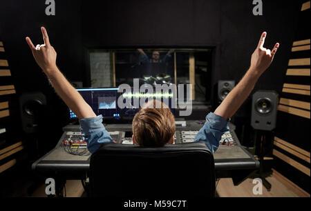 Hombre en consola de mezclas en el estudio de grabación de música