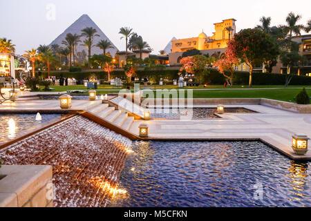 Tarde o vista nocturna de la Mena House Hotel, con las pirámides de Giza, en el fondo, El Cairo, Egipto, Norte de África