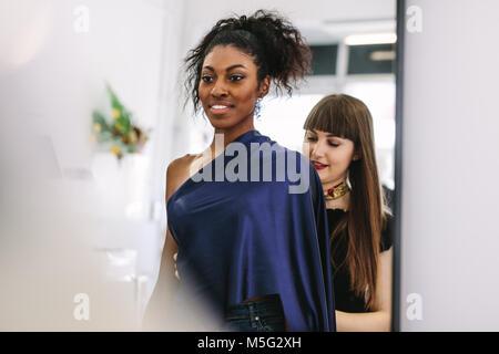 Joven diseñador de moda trabajando en sus diseños con un modelo. Mujer emprendedora en su tela shop diseñar ropa nueva.