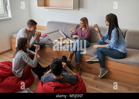 Grupo de estudiantes en un dormitorio comer pizza juntos Foto de stock