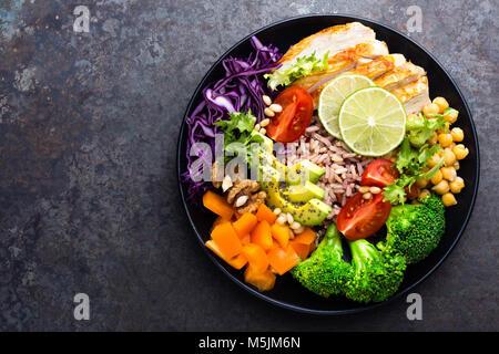 Tazón de buda plato con pechuga de pollo, arroz, aguacate, pimiento, tomate, brócoli, repollo, garbanzos, ensalada de lechuga fresca, piñones y nueces Foto de stock