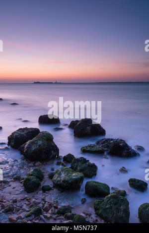 Un hermoso y tranquilo paisaje atmosférico o paisaje de la costa de la Isla de Wight en Sunset con rocas en la zona del embalse y tranquilo mar místico.