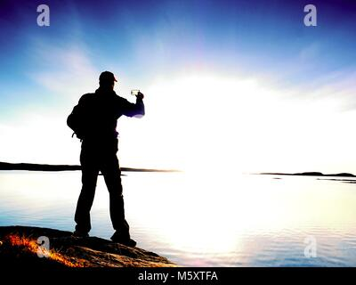 Silueta de hombre conservar recuerdos con la cámara del teléfono en su mano. Maravillosa puesta de sol en el mar, buen nivel de agua