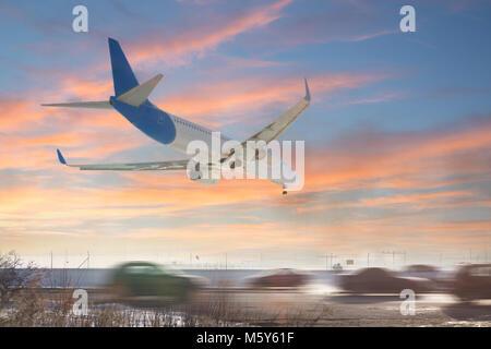 Vista trasera del avión aterrizando. Aviones que volaban sobre la carretera. Carretera con tráfico alto cerca de la pista del aeropuerto. El tipo de transporte en comparación. Concepto de viaje