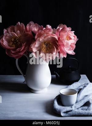 Encanto Coral peonías en flor, en una jarra blanca sobre la mesa con taza y tetera tetsublin, fondo oscuro, rodada Foto de stock