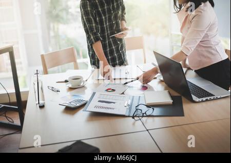 La empresaria asiática y debatir ideas con jóvenes hombre freelance en la sala de reuniones. Empresa co-operar con externalizar el concepto de trabajador.