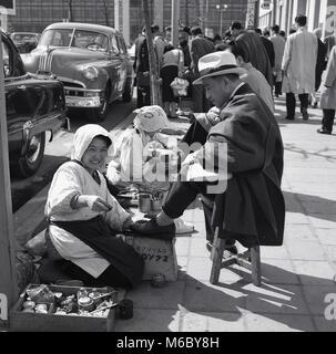 1950 histrocial, Tokio, las empresas japonesas hombres sentados en el pavimento herramientas om obteniendo un lustre de las trabajadoras fuera en la calle.
