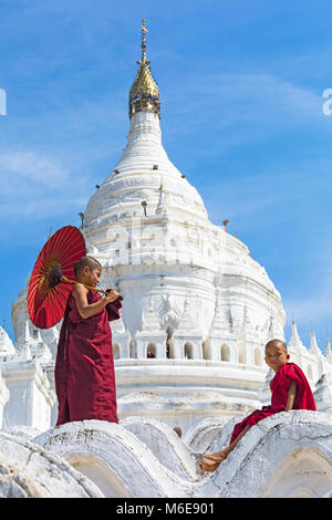 Joven novicio monjes budistas, uno sosteniendo una sombrilla y uno sentado en la Pagoda Myatheindan (también conocida como la Pagoda de Hsinbyume), Mingun, Myanmar (Birmania) Asia