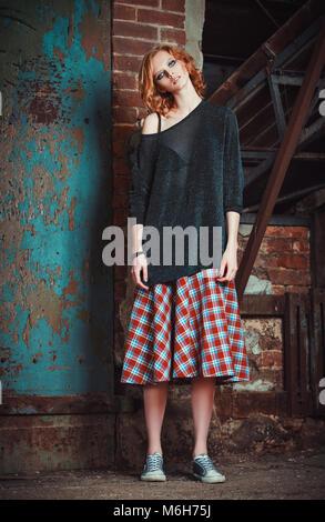 Grunge moda: retrato de una joven y bella chica pelirroja en el Plaid falda y suéter Foto de stock