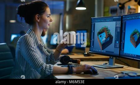 Game Developer femenina trabaja en un plano de diseño en su ordenador personal con dos pantallas, ella trabaja hasta tarde y bebidas de café. Oficina Loft creativo