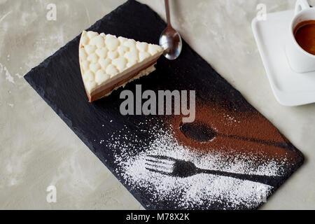 El esbozo del tenedor y cuchara , se espolvorea con cacao en polvo. Pastel de chocolate tres sobre un pedestal de piedra y café