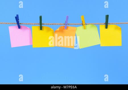 Notas rápidas de oficina en blanco colgando de una cuerda o línea de lavado