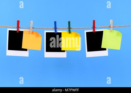 Cámara instantánea impresiones fotográficas en blanco y office Sticky notes colgando de una cuerda o cadena aisladas contra un fondo azul. Espacio para copiar.