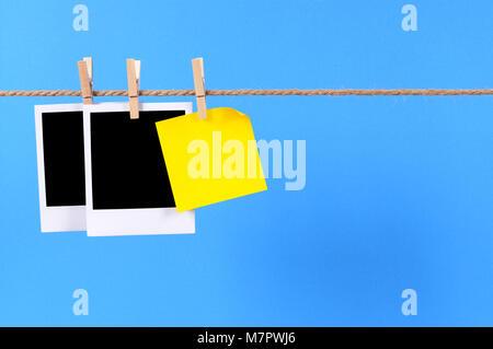 Cámara instantánea impresiones fotográficas en blanco y una oficina sticky note colgando de una cuerda o cadena aisladas contra un fondo azul. Espacio para copiar.