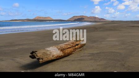 Graciosa, visto desde Lanzarote, inicie sesión en la playa