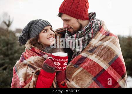 Romántica pareja joven envuelto en una manta, mientras que las compras de Navidad árbol del bosque