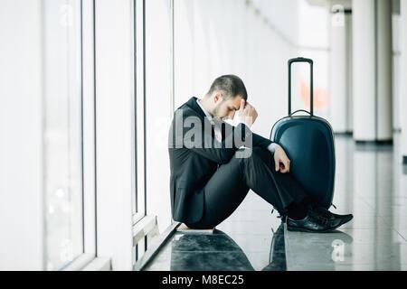 Hombre de negocios sentado en la terminal del aeropuerto en el suelo con la maleta con retraso en el vuelo, dos manos tocan en la cabeza, dolor de cabeza, a la espera de viajar.