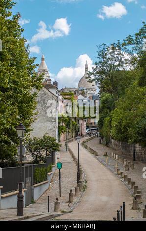 Vista del serpenteante camino huyendo entre veredas pavimentadas y árboles verdes en la calle con la arquitectura antigua en París, Francia