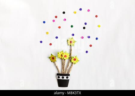 Arte de papel de colores, flores amarillas sobre un jarrón con deoration sobre fondo blanco.