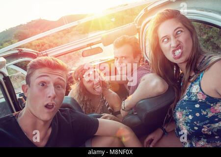 Grupo de gente feliz en un coche al atardecer haciendo caras.