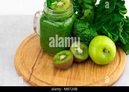 Saludable batido verde con espinacas en una jarra termo con ingredientes sobre fondo de madera.