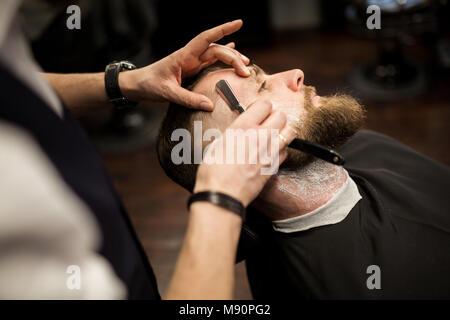 Retrato de joven siendo afeitado por peluquero profesional