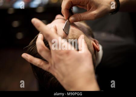 Retrato de arriba de cliente se afeitó por peluquero profesional