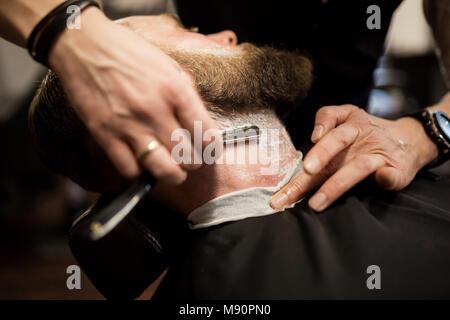 Retrato del hombre barbado siendo afeitado con maquinilla de afeitar