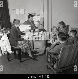 1950, foto histórica. SALUD.. una pareja joven con sus dos niños sentados tras una discusión o consulta con su médico local o GP, Inglaterra, Reino Unido.