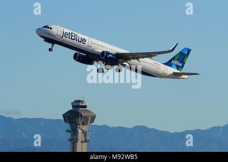JetBlue Airways Airbus A321 jet despegando de Pasajeros del Aeropuerto Internacional de Los Angeles, LAX. La Torre de Control y montañas San Gabriel detrás.