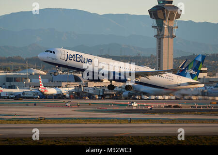 JetBlue Airways Airbus A321 avión jet despegando desde el Aeropuerto Internacional de Los Angeles, LAX, temprano en la mañana, la nueva torre de control detrás.