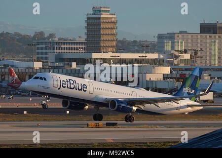 JetBlue Airways Airbus A321 avión jet despegando desde el Aeropuerto Internacional de Los Angeles, LAX, temprano en la mañana, la vieja torre de control detrás.