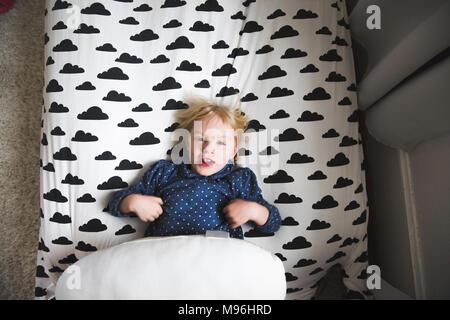 Chica acostado en la cama con adhesivo de cloud Foto de stock