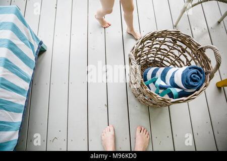 Cesta de mimbre con toallas, junto a los pies de los niños