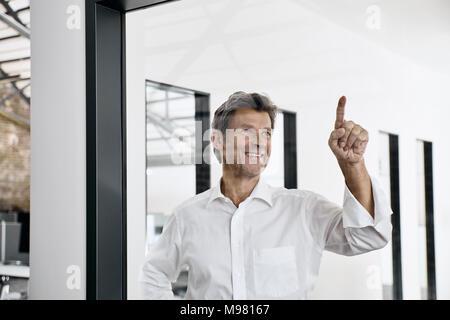 Sonriente empresario maduro tocar cristal en oficina moderna