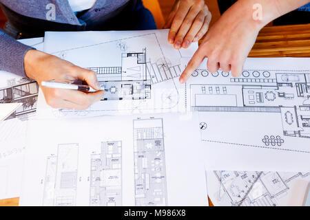 El equipo de arquitectos que trabajan en un proyecto, discutiendo blueprints