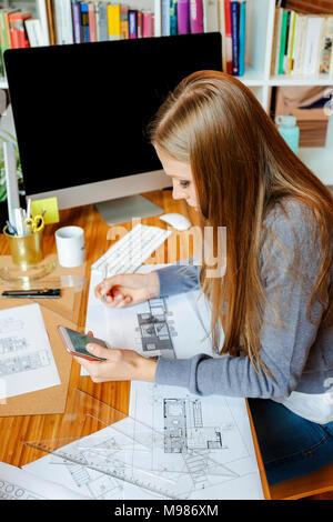 Joven que trabaja en la oficina de arquitectura, utilizando el teléfono Foto de stock