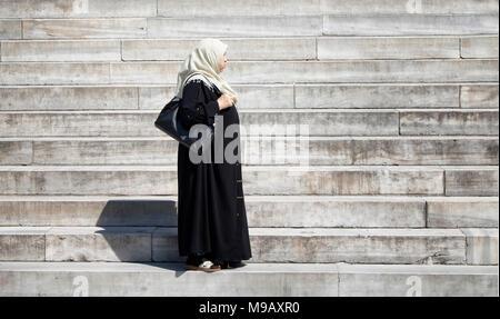 Edad media musulmana llevar el hijab de pie en las escaleras de la mezquita histórica llamada 'Yeni Cami' en Estambul. Foto de stock