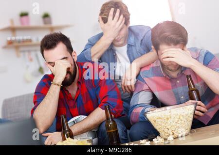 Imagen del triste amigos varones viendo deportes en la televisión en casa